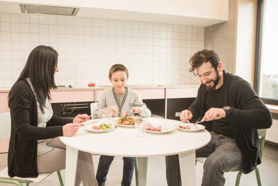 Gezin eet slaatje in de gastenkeuken