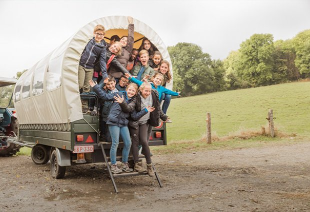 Schoolkinderen in huifkar