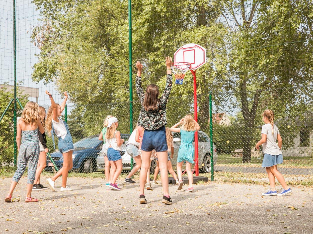 Groep jongeren speelt basketbal