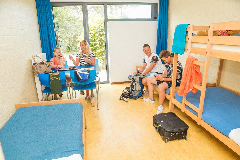 Familie met twee kinderen in een kamer