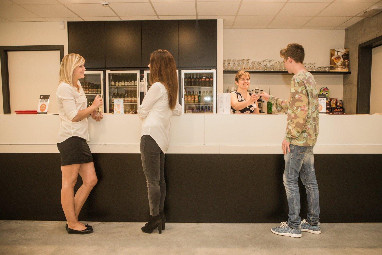 Drie jongeren drinken iets aan de bar