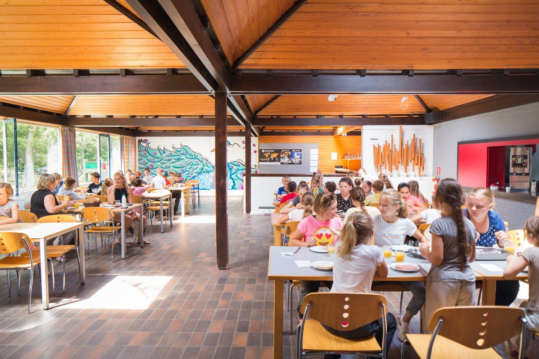 Groep kinderen aan het eten in de eetzaal