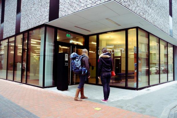 Twee backpackers aan de ingang van hostel De Ploate